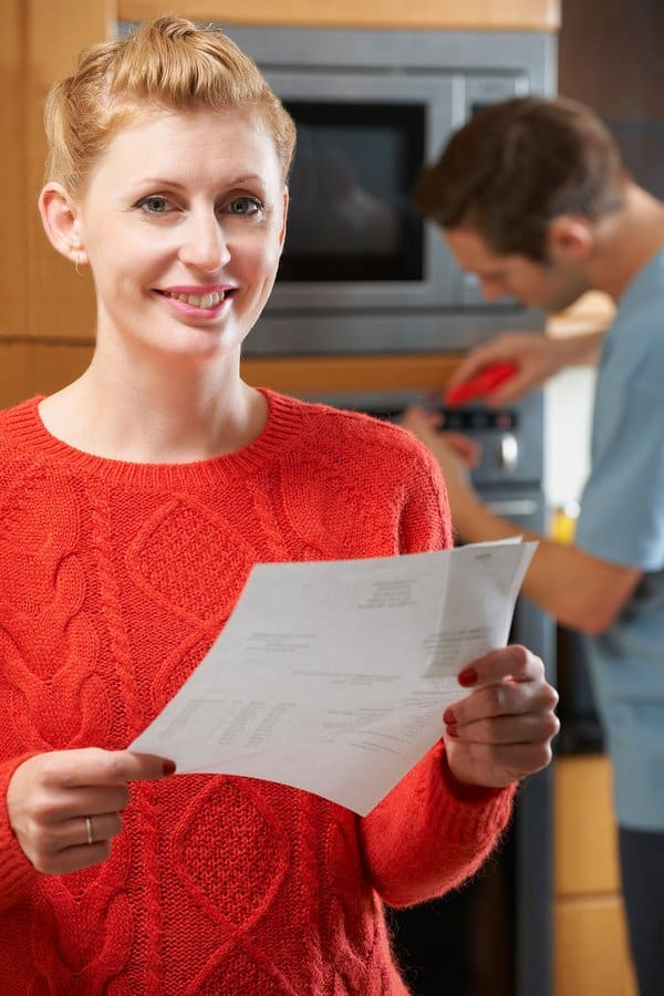 Portrait Of Smiling Woman With Repair Bill